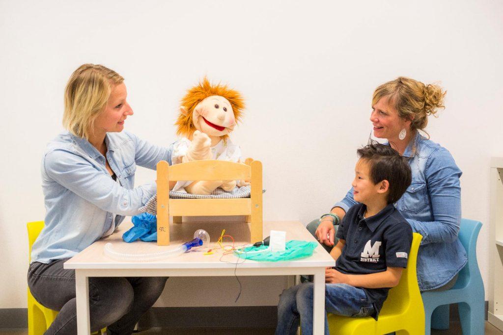 Dokter, joep en mama spelen met pop