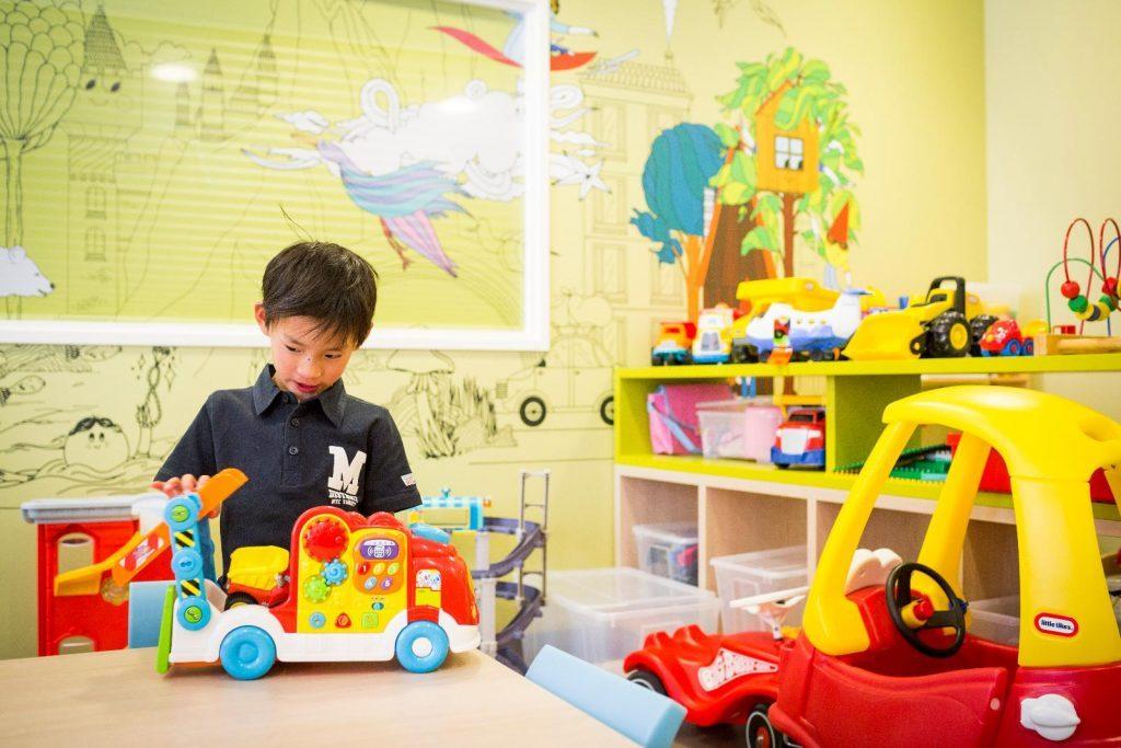 Joep speelt met auto in de speelkamer