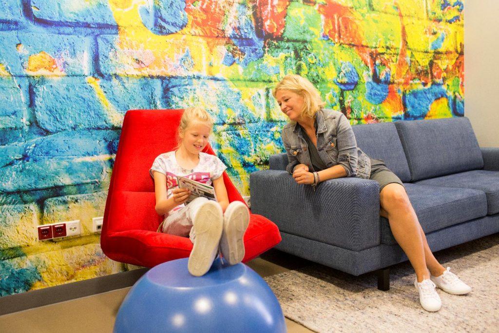 Meisje leest boekje met mama in lounge